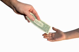 The hand of a child who receives the weekly allowance from an adult.